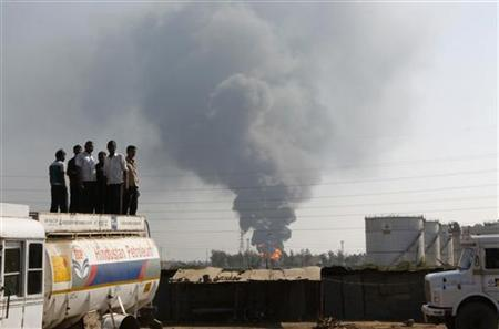 Smoke and flames billow from Indian Oil Corporation's fuel depot as onlookers stand atop an oil tanker in Hazira, near Surat in Gujarat January 5, 2013. REUTERS/Amit Dave