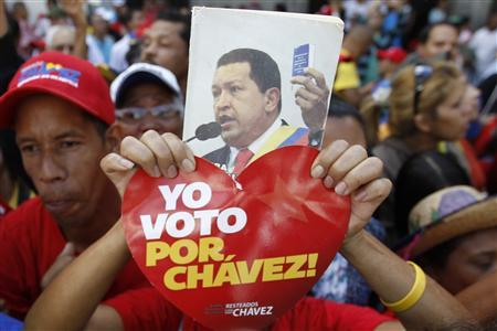 A supporter of Venezuela's President Hugo Chavez holds up a picture of him during the inauguration of the National Assembly in Caracas January 5, 2013. Chavez's formal swearing-in for a new six-year term scheduled for January 10 can be postponed if he is unable to attend due to his battle to recover from cancer surgery, Venezuela's Vice President Nicolas Maduro said on Friday. REUTERS/Carlos Garcia Rawlins