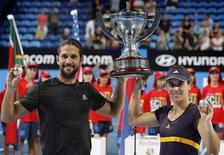Fernando Verdasco (L) and Anabel Medina Garrigues of Spain hold up the Hopman Cup and their diamond encrusted silver balls after defeating Novak Djokovic and Ana Ivanovic of Serbia in the final of the Hopman Cup tennis tournament in Perth January 6, 2013. REUTERS/Stringer