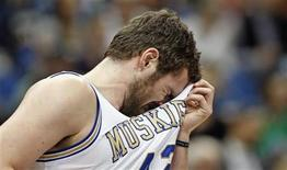 Minnesota Timberwolves forward Kevin Love (42) wipes sweat from his face during the first half of the Timberwolves' NBA basketball game against the Los Angeles Clippers in the Target Center in Minneapolis, March 5, 2012. REUTERS/Eric Miller