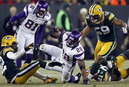 Minnesota Vikings running back Adrian Peterson (28) is brought down by Green Bay Packers inside linebacker Brad Jones (59) during their NFL NFC wildcard playoff football game in Green Bay, Wisconsin January 5, 2013. REUTERS/Tom Lynn