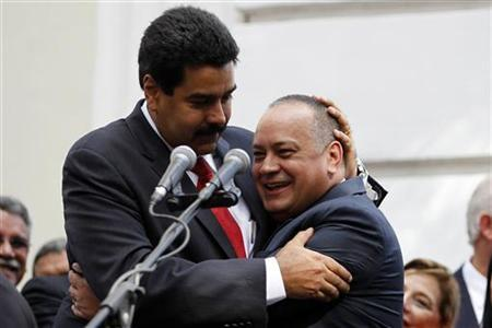 Venezuelan Vice President Nicolas Maduro (L) embraces National Assembly President Diosdado Cabello during the assembly inauguration in Caracas January 5, 2013. Venezuelan lawmakers re-elected a staunch ally of Hugo Chavez to head the National Assembly on Saturday, putting him in line to be caretaker president if the socialist leader does not recover from cancer surgery. By choosing the incumbent, Cabello, the ''Chavista''-dominated legislature cemented the combative ex-soldier's position as the third most powerful figure in the government, after Chavez and Vice President Maduro. REUTERS/Carlos Garcia Rawlins (VENEZUELA - Tags: POLITICS)