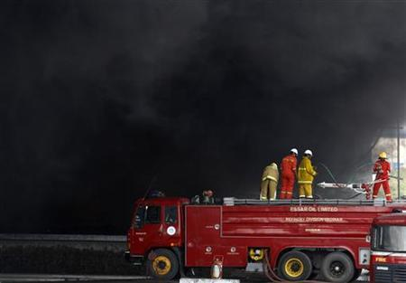 Firefighters try to douse the fire as smoke billows from Indian Oil Corporation's fuel depot in Hazira in Gujarat January 6, 2013. REUTERS/Amit Dave