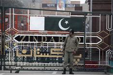 A paramilitary soldier stands guard beside a border gate at the India-Pakistan joint check-post at the Wagah border near Lahore January 6, 2013. REUTERS/Mohsin Raza