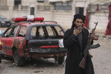 A Free Syrian Army fighter smokes a cigarette while posing with his weapon in front of a damaged car in Aleppo January 5, 2013. REUTERS/Muzaffar Salman (SYRIA - Tags: CONFLICT)