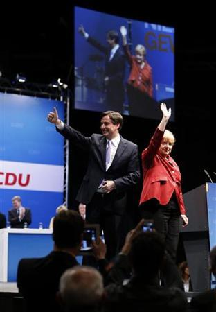 German Chancellor and Christian Democratic Union (CDU) party leader Angela Merkel, Lower Saxony federal state premier and top candidate of the CDU in the federal state elections David McAllister (L) wave after their speeches during the CDU's initial election campaign event in Brunswick, January 5, 2013. A regional election will be held on January 20 in Lower Saxony state, with Merkel's conservatives fighting to prevent a loss of local power to their Social Democrat rivals that could dent the chancellor's 2013 re-election hopes. REUTERS/Morris Mac Matzen (GERMANY - Tags: POLITICS ELECTIONS)