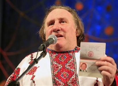 French film star Gerard Depardieu, wearing a local costume, shows his passport during a ceremony in the town of Saransk in the Mordoviya Republic, southeast of Moscow, January 6, 2013. Depardieu received a hug from Russia's President Vladimir Putin and a new Russian passport on Sunday after abandoning his homeland to avoid a new tax rate for millionaires. REUTERS/Yulia Chestnova