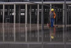 A worker walks outside the main terminal of the Berlin-Brandenburg international airport (BER) outside Berlin, November 1, 2012. REUTERS/Thomas Peter