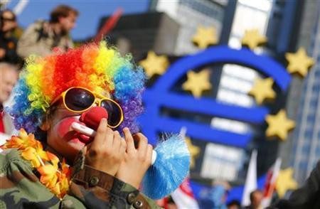 A demonstrator dressed as a clown sits next to the euro sculpture in front of the headquarters of the European Central Bank (ECB) during an anti-capitalism demonstration in Frankfurt, September 29, 2012. REUTERS/Kai Pfaffenbach/Files