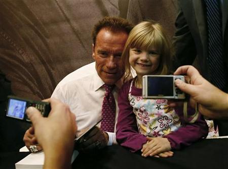 Actor and former California governor Arnold Schwarzenegger poses with a girl during the signing of his book 'Total Recall' at the book fair in Frankfurt, October 10, 2012. REUTERS/Ralph Orlowski/Files