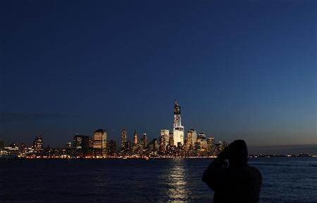 A man photographs the skyline of Lower Manhattan in New York from a park along the Hudson River in Hoboken, New Jersey, December 28, 2012. REUTERS/Gary Hershorn