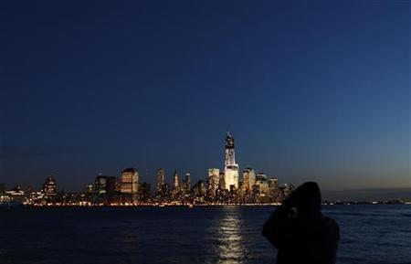 A man photographs the skyline of Lower Manhattan in New York from a park along the Hudson River in Hoboken, New Jersey, December 28, 2012. REUTERS/Gary Hershorn