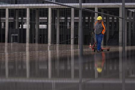 A worker walks outside the main terminal of the Berlin-Brandenburg international airport (BER) outside Berlin, November 1, 2012. REUTERS/Thomas Peter (GERMANY - Tags: TRANSPORT BUSINESS)