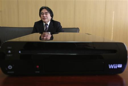 Nintendo Co's President Satoru Iwata speaks next to the company's Wii U game console during an interview with Reuters at the company headquarters in Kyoto, western Japan January 7, 2013. Nintendo's year-end sales of its Wii U games console were steady, though not as strong as when its Wii predecessor was first launched, Iwata said on Monday. REUTERS/Yuriko Nakao