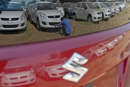 A worker cleans a Maruti Suzuki Swift Dzire car as he is being reflected on a car at the company's stock yard at Sanand in Gujarat October 30, 2012. REUTERS/Amit Dave/Files