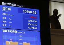 El índice japonés Nikkei bajó el lunes, cortando con cinco sesiones de subidas, después de que una pausa en la debilidad del yen desencadenaba tomas de beneficios en exportadoras, mientras las eléctricas perdían terreno por rebajas de notas de analistas. En la imagen, un hombre junto a un panel electrónico en la bolsa de Tokio, el 28 de diciembre de 2012. REUTERS/Kim Kyung-Hoon