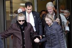 Il segretario di Stato Usa Hillary Clinton (a sinistra) lascia il New York Presbyterian Hospital con il marito Bill (a destra) e la figlia Chelsea. REUTERS/Joshua Lott