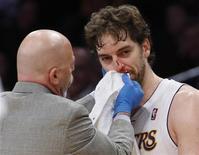 Los Denver Nuggets hundieron a Los Angeles Lakers más en la depresión al ganar el domingo por 112 a 105 pese a los fuegos artificiales de Kobe Bryant en el último cuarto. Los Lakers (que suman 15 victorias y 18 derrotas) sufrieron más que heridas en el orgullo, ya que Pau Gasol tuvo que abandonar la cancha en el último cuarto tras un golpe con el codo de JaVale McGee que le dejó sangrando por la nariz. En la imagen, Gasol atendido tras recibir el golpe en la nariz, el 6 de enero de 2013. REUTERS/Danny Moloshok