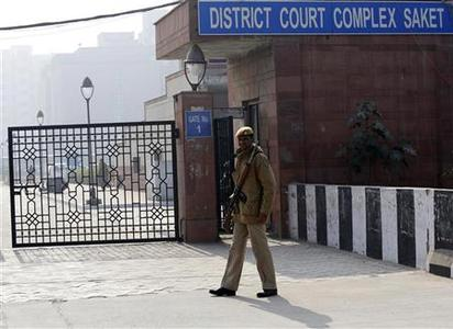 A policeman keeps guard outside a court in New Delhi January 7, 2013. Five men accused of the gang rape and murder of an Indian student appeared in court on Monday to hear charges against them, after two of them offered evidence possibly in return for a lighter sentence in the case that has led to a global outcry. The five men, along with a teenager, are accused of raping the 23-year-old physiotherapy student on a bus in New Delhi. She died two weeks later on December 28 in a Singapore hospital. REUTERS/Adnan Abidi