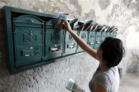 A woman puts leaflet in letter boxes in Naples April 3, 2012. REUTERS/Ciro De Luca/Files