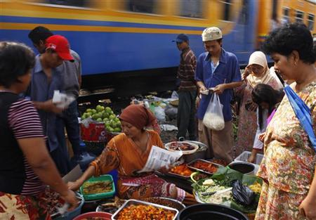 A street vendor serves her costumer near a railway track at Duri district in Jakarta, September 30, 2011. REUTERS/Beawiharta