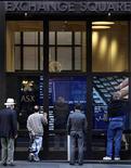 Dei passanti guardano l'andamento del mercato azionario su un monitor all'ingresso della Borsa australiana a Sydney. REUTERS/Tim Wimborne