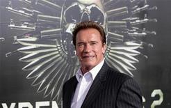 """Ator e ex-governador da Califórnia Arnold Schwarzenegger posa para fotos na estréia do filme """"Mercenários 2"""" em Hollywood, em agosto. Schwarzenegger, conhecido por sua participação em filmes de ação, acha que a violência exibida nas telas de cinema é mero entretenimento, sem qualquer relação com incidentes trágicos como o recente massacre de 20 crianças em uma escola de Connecticut. 15/08/2012 REUTERS/Mario Anzuoni"""