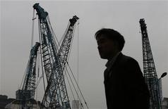 A man walks past cranes at a construction site in a business district in Tokyo December 28, 2012. REUTERS/Kim Kyung-Hoon (JAPAN - Tags: BUSINESS CONSTRUCTION POLITICS)