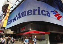 Tourists walk past a Bank of America banking center in Times Square in New York in this June 22, 2012 file photograph. Bank of America Corp said it will pay $3.6 billion to Fannie Mae to settle claims related to residential mortgage loans for the nine years to the end of 2008. REUTERS/Brendan McDermid/Files