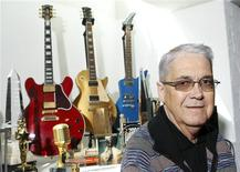 Montreux Jazz Festival founder Claude Nobs posing near a guitar given to him by blues legend B. B. King (red) and other instruments and awards after an interview with Reuters in his chalet in Caux in this April 21, 2010 file photograph. REUTERS/Denis Balibouse/Files