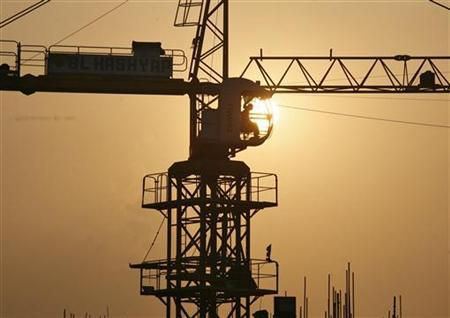 A worker sitting inside a crane is silhouetted against the setting sun at the construction site of a commercial complex in Noida, in Uttar Pradesh September 21, 2011. REUTERS/Parivartan Sharma/Files