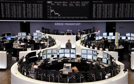 Traders are pictured at their desks in front of the DAX board at the Frankfurt stock exchange January 2, 2013. REUTERS/Remote/Joachim Herrmann (GERMANY - Tags: BUSINESS)