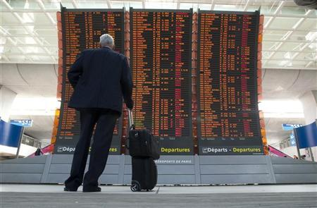 A passenger looks at flight departure information board at Charles-de-Gaulle airport in Roissy near Paris April 20, 2010. REUTERS/Gonzalo Fuentes