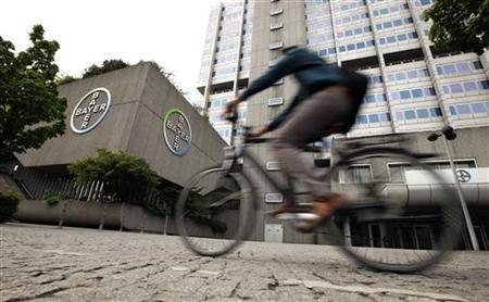 A man rides a bicycle in front of the building of Germany's largest drugmaker Bayer HealthCare Pharmaceuticals in Berlin April 28, 2011. The German drugmaker raised its full-year sales and earnings outlook on strong demand for its pesticides, as high prices for agricultural commodities drive spending by farmers. REUTERS/Fabrizio Bensch (GERMANY - Tags: BUSINESS HEALTH)
