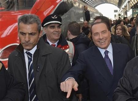 Former Italian Prime Minister Silvio Berlusconi (R) gestures as he arrives at Milan train station December 29, 2012. REUTERS/Paolo Bona
