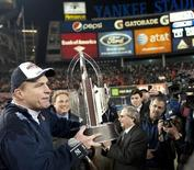 Syracuse University head coach Doug Marrone holds the championship trophy after they beat Kansas State University in their NCAA football Pinstripe Bowl game at Yankee Stadium in New York, December 30, 2010. REUTERS/Ray Stubblebine