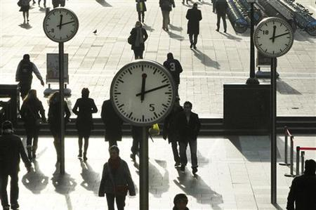 Workers walk past clocks showing a time of 12 minutes past 12 noon, on this century's last sequential date, in a plaza in the Canary Wharf business district of London December 12, 2012. REUTERS/Toby Melville