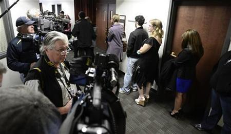 Family members of victims wait for a second security check in the hall with members of the media after arriving for a court appearance of James Holmes, accused shooter in the July 20, 2012 theater shootings, in Centennial, Colorado January 7, 2013. REUTERS/Mark Leffingwell