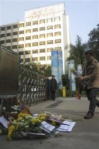 A man lays a bouquet of chrysanthemums in front of the headquarters of Southern Weekly newspaper in Guangzhou, Guangdong province, January 7, 2013. REUTERS-James Pomfret