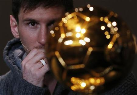 Lionel Messi of Argentina looks at the Ballon d'Or trophy during a news conference at the Kongresshaus in Zurich January 7, 2013. REUTERS/Michael Buholzer