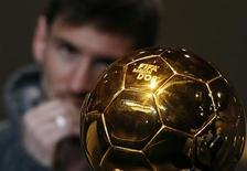 FIFA Men's Ballon d'Or of the Year 2012 nominee Lionel Messi of Argentina watches the trophy during a news conference before the FIFA Ballon d'Or 2012 soccer awards ceremony at the Kongresshaus in Zurich January 7, 2013. REUTERS/Michael Buholzer