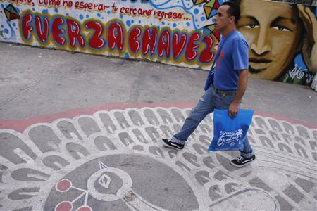 A man walks past a graffiti depicting Venezuelan President Hugo Chavez in Caracas January 7, 2013. The wall reads: 'Force Chavez'. REUTERS/Jorge Silva