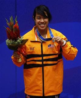 Nicol Ann David of Malaysia holds her gold medal after winning the women's single squash final at the 16th Asian Games in Guangzhou, Guangdong province, November 21, 2010. REUTERS/Mick Tsikas