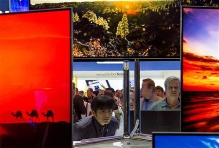People look at Samsung flat screen TVs in Berlin, August 31, 2012. REUTERS/Thomas Peter