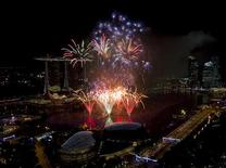 Fireworks explode over Marina Bay in front of the Marina Bay Sands casino and resort during a pyrotechnic show to welcome the new year in Singapore January 1, 2011. REUTERS/Vivek Prakash