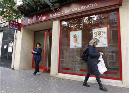 A woman leaves a branch of Banco de Valencia in central Valencia, November 28, 2012. REUTERS/Heino Kalis (SPAIN - Tags: BUSINESS EMPLOYMENT)