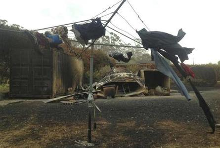 Clothes hang from a singed clothesline in a backyard affected by a bushfire at Boomer Bay, about 40 kilometres (24 miles) east of Hobart, January 8, 2013. REUTERS/Australian Broadcasting Corporation/Tyson Shine