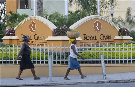 People walk in front of the new Royal Oasis Hotel in Port-au-Prince December 13, 2012. REUTERS/Swoan Parker