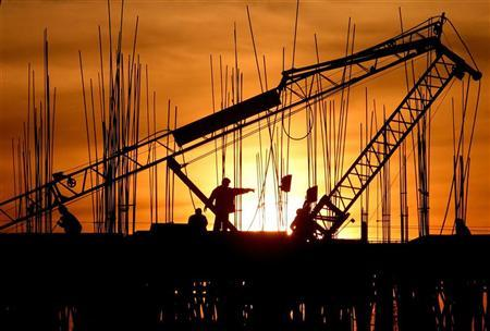 Construction workers work at a site as the sun sets in Chandigarh December 16, 2006. REUTERS/Ajay Verma/Files