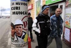 La moral entre las empresas de la zona euro mejoró nuevamente en diciembre, pero la tasa de desempleo alcanzó un nuevo récord y los hogares se abstuvieron de gastar en el período previo a la Navidad, lo que sugiere que la salida del bloque de la recesión será lenta. En la imagen, varias personas pasan junto a un cartel que demanda más trabajo en Zlatna, a 420 km al noroeste de Bucarest el 8 de diciembre de 2012. REUTERS/Radu Sigheti